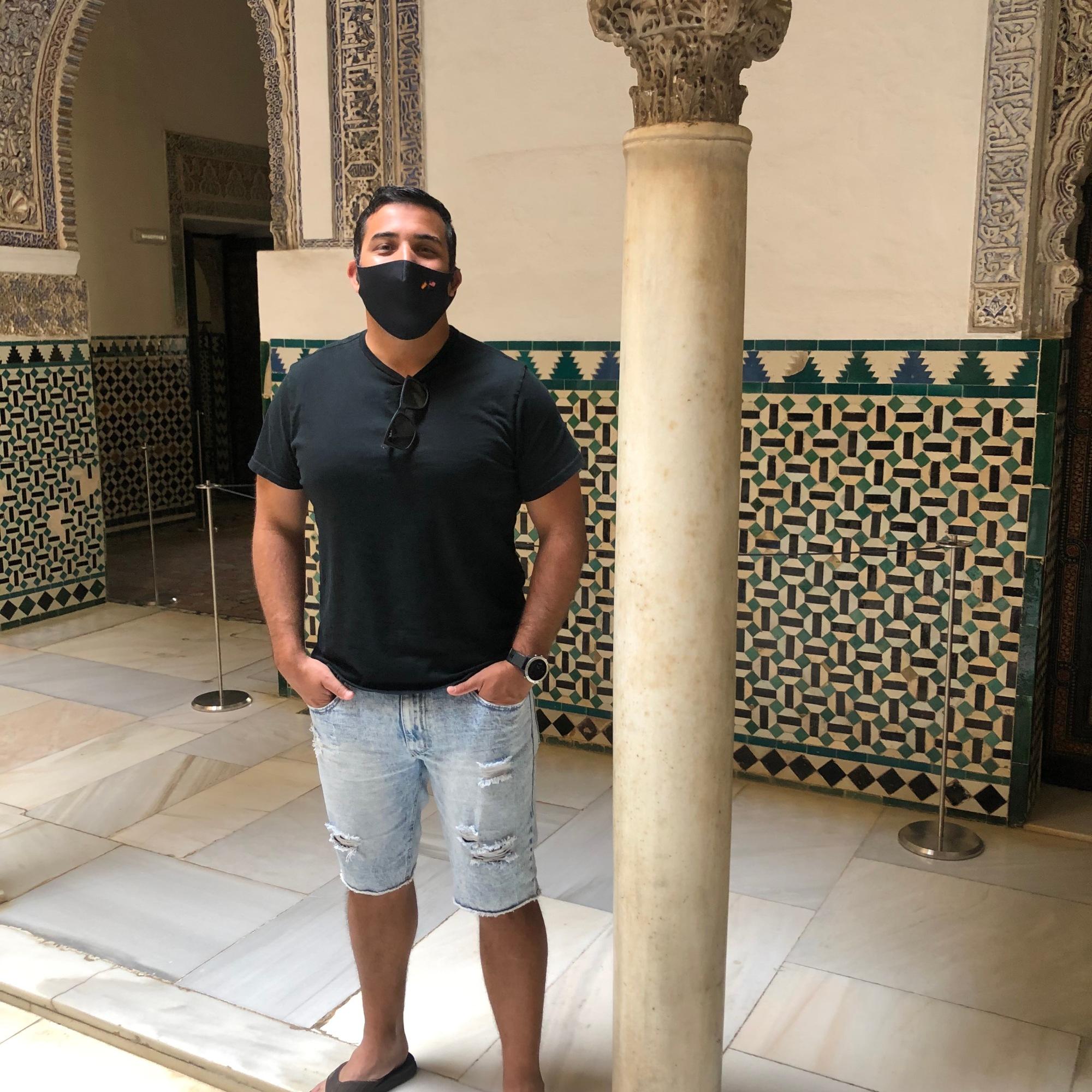 man standing next to a column in the Alcazar