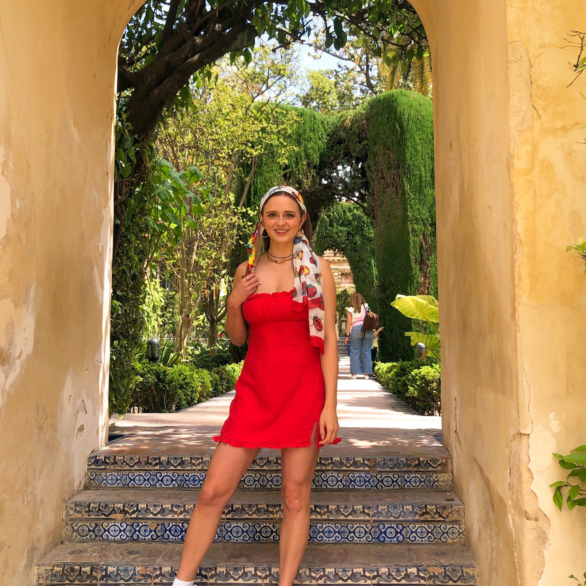 Standing under an arch in the Alcazar garden