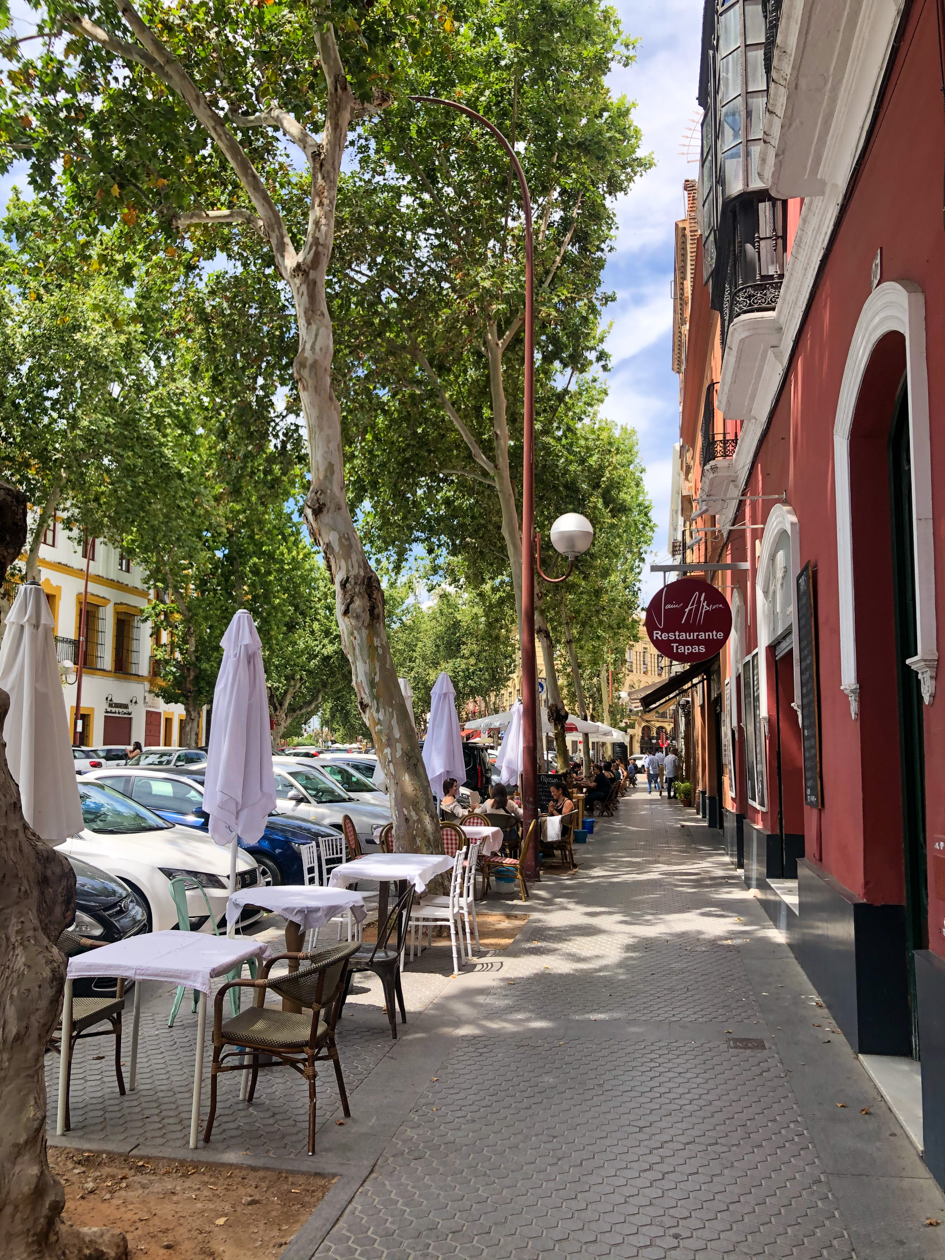 A sunny, cafe-lined street in Seville, Spain